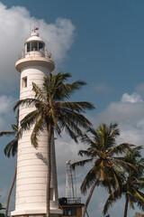 Biała latarnia morska na tle niebieskiego nieba i palm w miejscowości Galle na Sri lance.