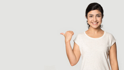 Obraz Portrait of smiling Indian woman isolated on grey studio background point at blank empty copy space. Happy millennial mixed race female show good promotion deal or sale discount. Commerce concept. - fototapety do salonu