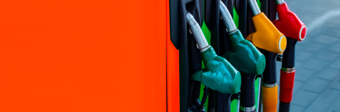 Gas station close-up with colored fuel hoses.