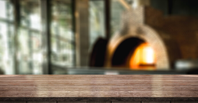 Empty Wooden Table On Blur Pizza Restaurant With Italian Wood Fired Oven Background.