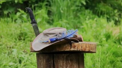 Obraz kapelusz z piórkiem na pniu survival  - fototapety do salonu