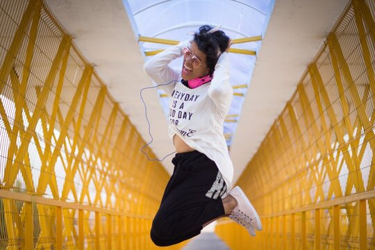 Portrait of a mid adult afro mexican woman screaming while jumping into the air