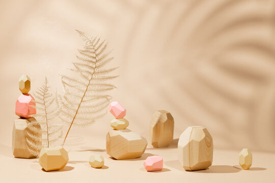 Composition of geometric balancing wooden stones and dried leaves. Concept of balance. Pastel background with copy space and shadow of tropical leaves.