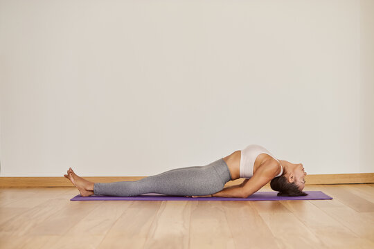 Woman performing Fish pose on yoga mat in room