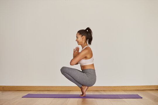 Content woman performing Squatting Toe Balance pose in room