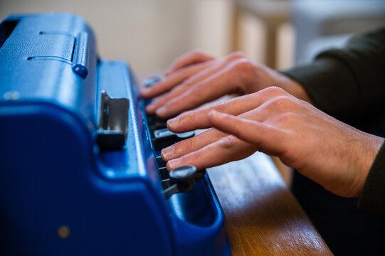 Blind man typing on typewriter with braille code