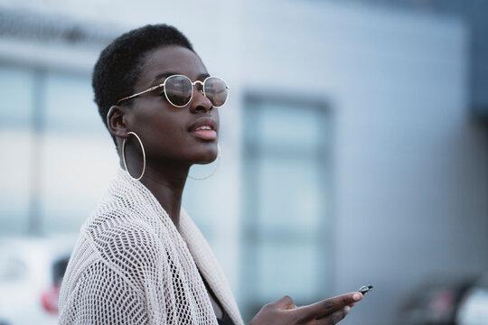 Stylish ethnic woman using smartphone in city