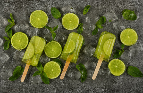 Frozen lime and mint ice popsicles on table