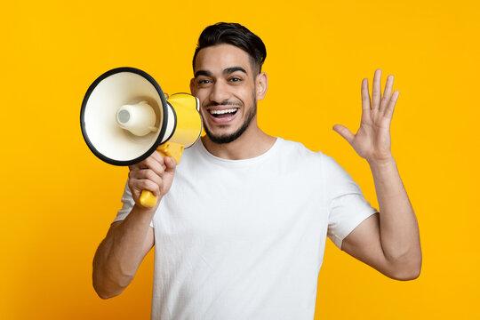 Excited arab guy speaking loud, using megaphone on yellow