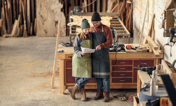 Couple of woodworkers discussing papers in workshop