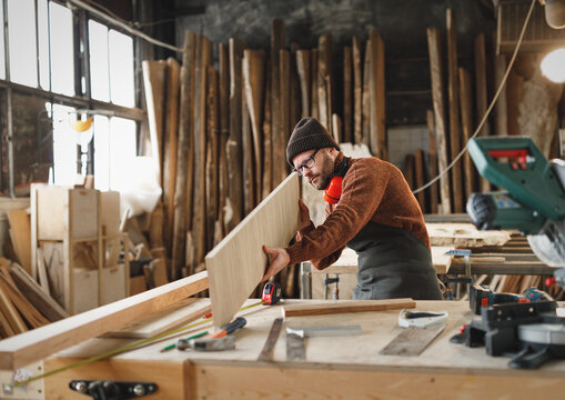 Craftsman examining wooden plank in workshop