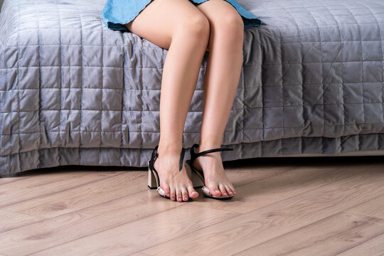 Tired woman takes off shoes after work at home, beauty female feet, body care concept