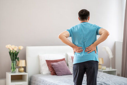 Back pain, kidney inflammation, man suffering from backache at home