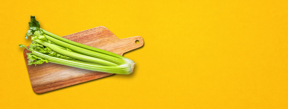 Celery branch bunch on a cutting board. Isolated on yellow banner background
