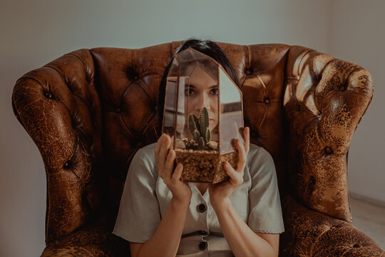 Woman looking at camera through plant in glass jar