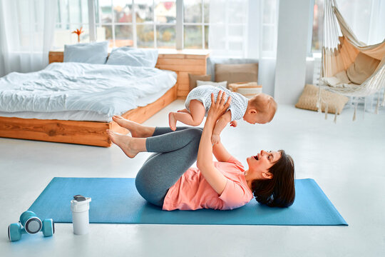 A sports mother is engaged with the child in fitness and yoga at home. The concept of sports, motherhood and an active lifestyle. Young woman in sports training with her child.