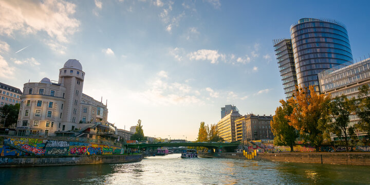 vienna, austria - OCT 17, 2019: architecture on donaukanal at sunset. water way betweein famous buildings of urania observatory and uniqa tower in evening light. popular travel destination in autumn