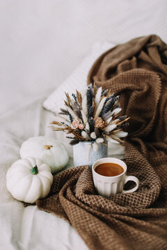 Autumn still life with a coffee cup with flowers and pumpkins on a cozy plaid in bed. Stylish autumn flat lay.
