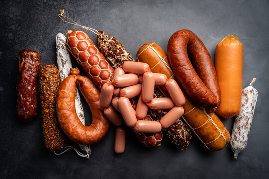 Set of different types of sausages, salami and smoked meat with basil and spices on a black background. Top view.