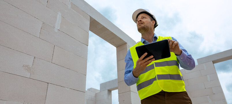 construction project monitoring - engineering supervisor working with digital tablet at building site. banner copy space