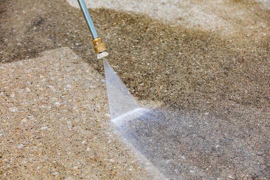 Pressure washing concrete driveway. Home cleaning, maintenance and household chores concept