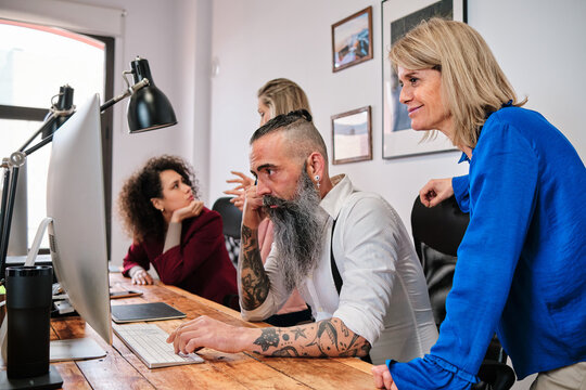 Hipster employee with multiracial colleagues working on desktop computer