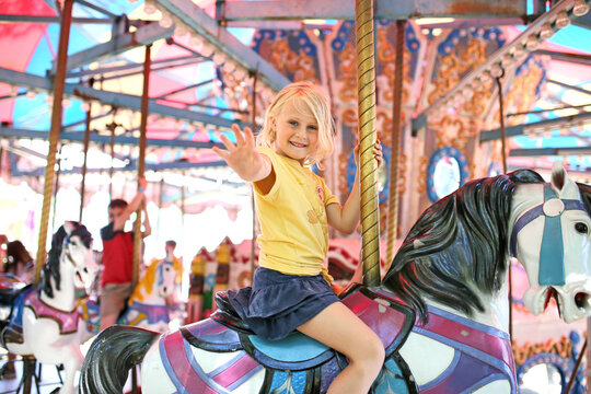 Happy Little Child On Merry Go Round Horse at Carnival