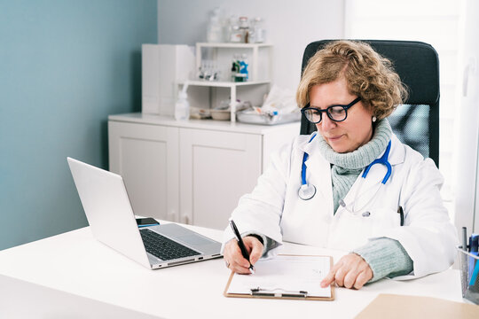 Physician writing on paper at table with tablet in hospital