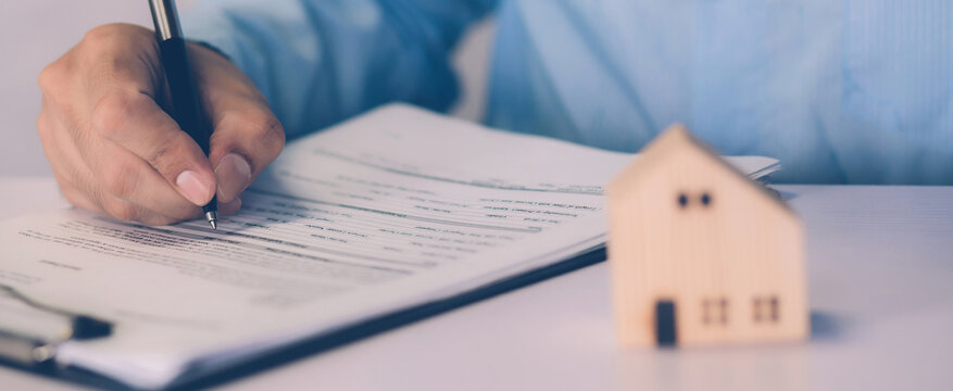 Real estate agent holding home and signing contract about agreement of real property on desk, house broker and planning investment, businessman writing on document form rent house, business concept.