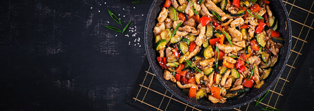 Stir fry with chicken, zucchini and sweet peppers - Chinese food. Top view, banner