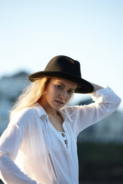 Carefree young blonde-haired woman at beach wearing black hat