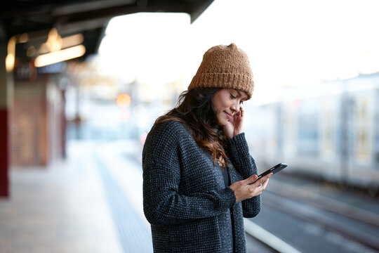 Asian woman checking messages waiting at train station