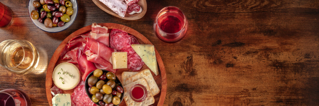 Charcuterie and cheese board panorama with red wine and olives, shot from the top on a rustic background with copy space. Spanish tapas or Italian antipasti