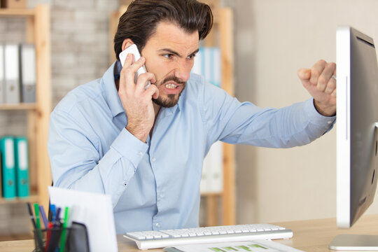 businessman complaining on the phone about problems with laptop