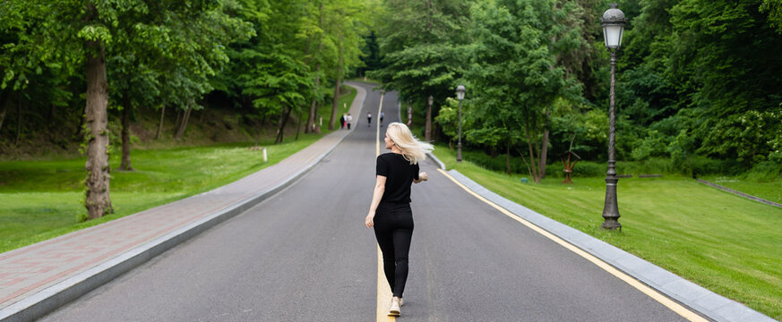 Joyful young lady in casual clothes walking along asphalt road in countryside, hitchhiking for ride outdoors. Lovely millennial woman traveling alone by autostop