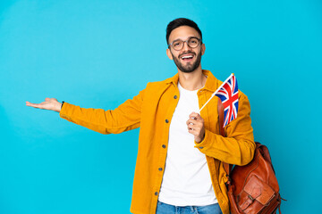 Obraz Young caucasian man holding an United Kingdom flag isolated on yellow background extending hands to the side for inviting to come - fototapety do salonu