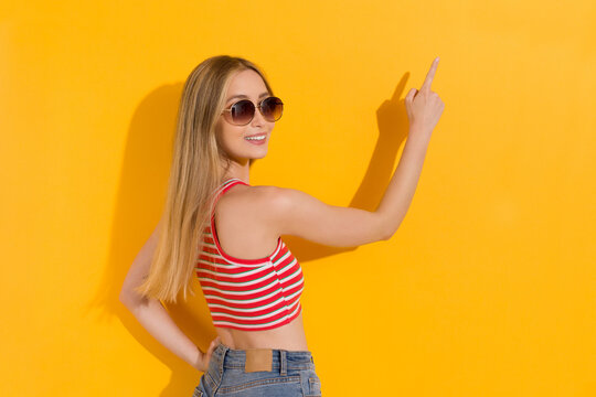 Smiling Young Woman In Striped Tank Top And Sunglasses Is Pointing.