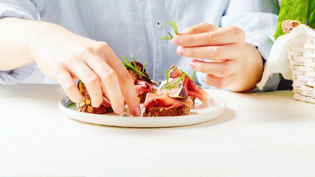 Female hand holds rosmarinon bruschetta with raw ham and fresh fig.