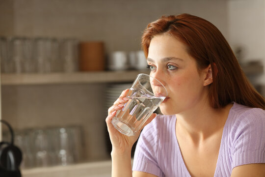 Woman drinking water from glass in the kitchen