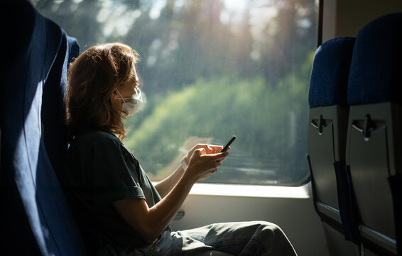 Young woman in a protective mask sitting in a train with a smartphone in her hands. Taking care of health and travel during a pandemic