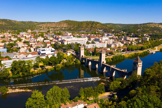 Picturesque summer drone view of ancient fortified stone arch bridge Pont Valentre crossing Lot River in Cahors, Occitanie, France..