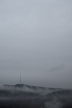 Gloomy cloudy weather. Fog over the forest on the hill. Place for text