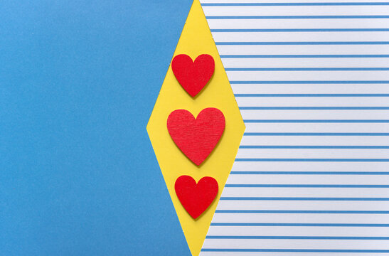 solid blue and blue striped paper background featuring three red hearts on a yellow diamond space at centre