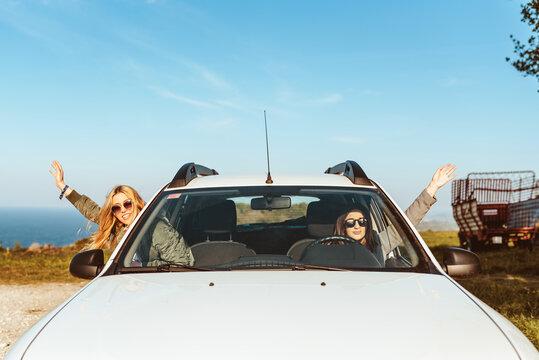 Happy women in car on shore