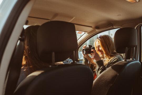 Woman taking photo of friend in car