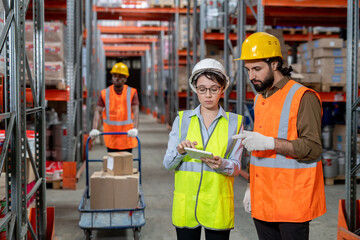 Obraz Two warehouse employees with tablet discussing working points - fototapety do salonu