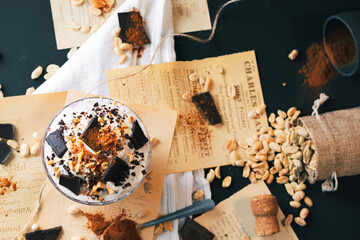 Fototapeta Dessert. Yoghurt dessert with chocolate and peanuts. Vintage dessert with cinnamon. Dessert served on a newspaper. obraz