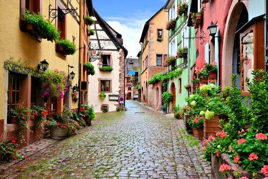 Quaint colorful cobblestone lane in the Alsatian town of Riquewihr, France