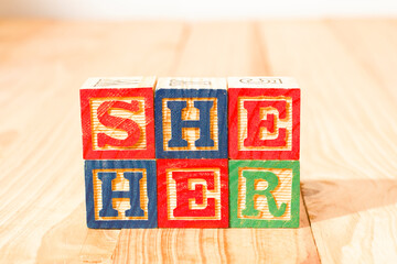 Fototapeta Spectacular wooden cubes with the word SHE HER on a wooden surface. obraz