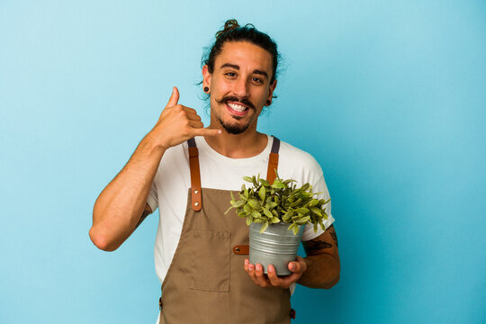 Young gardener caucasian man holding a plant isolated on blue background showing a mobile phone call gesture with fingers.